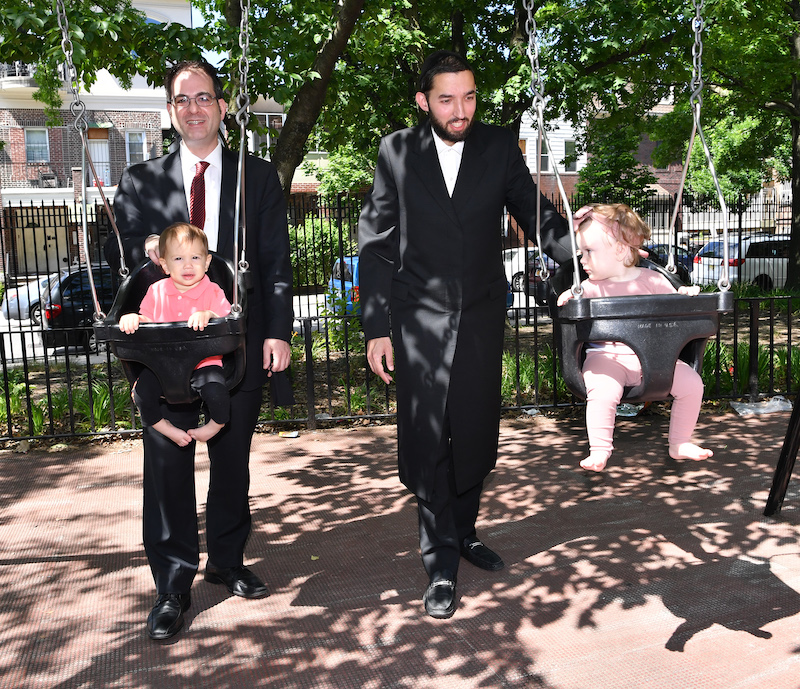 City Councilman Kalman Yeger, left, and Assemblyman Simcha Eichenstein, right, push young chilren on the swings at the Dome Playground. Contributed photo.