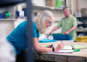 Senior businesswoman is doing paperwork in her stock warehouse. Her husband is in the background measuring fabric.