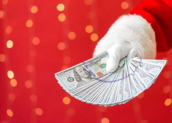 Santa holding US dollar bills on a shiny light red background