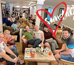 This is a photograph of some people enjoying a Kingston LGBT Forum coffee morning at a café. The photograph is overlaid with the outline of a red heart and the word 'Sunday'