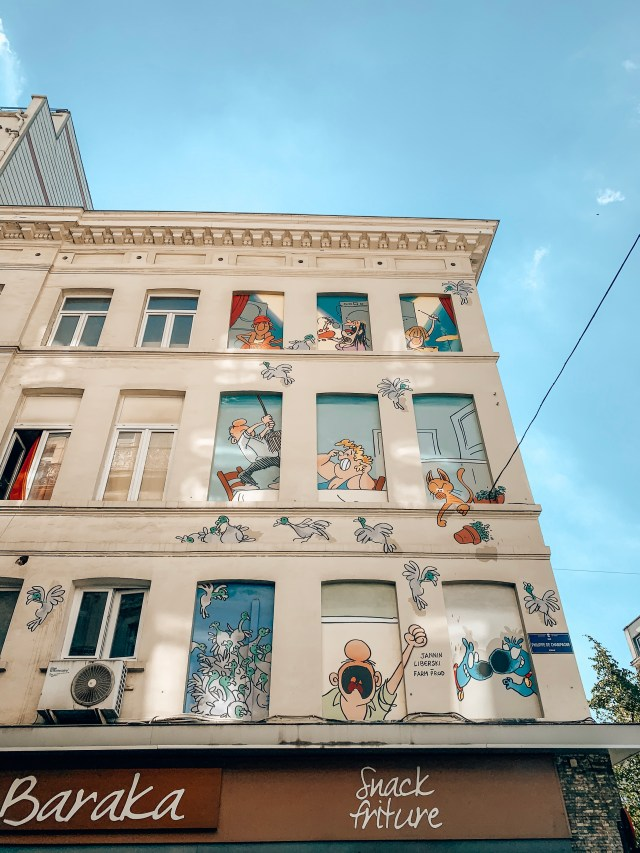 A mural showing many comic book characters in the boarded up windows of a building, from Belgian comic Froud & Stouf