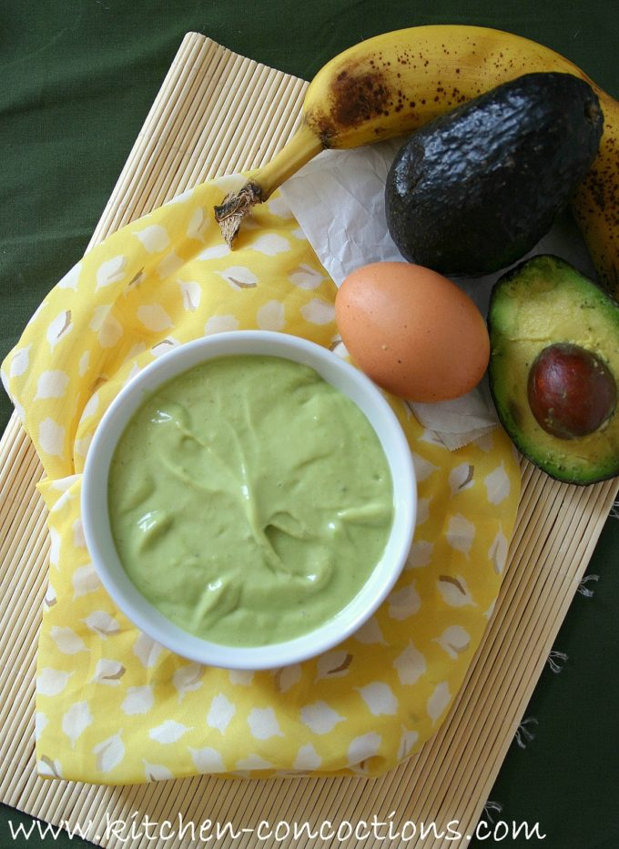 homemade avocado hair mask in a white bowl with a yellow and white towel underneath and the hair mask ingredients, eggs, avocado and banana sitting next to the bowl