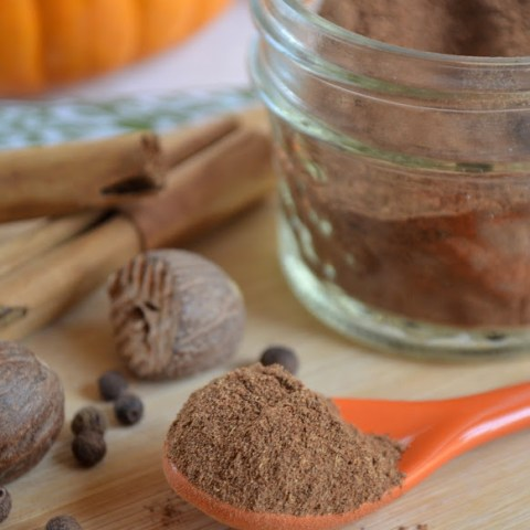 close up shot of homemade pumpkin pie spice recipe in an orange spoon with a jar of the spice blend, whole cinnamon, nutmeg and cloves and mini pumpkins in the background