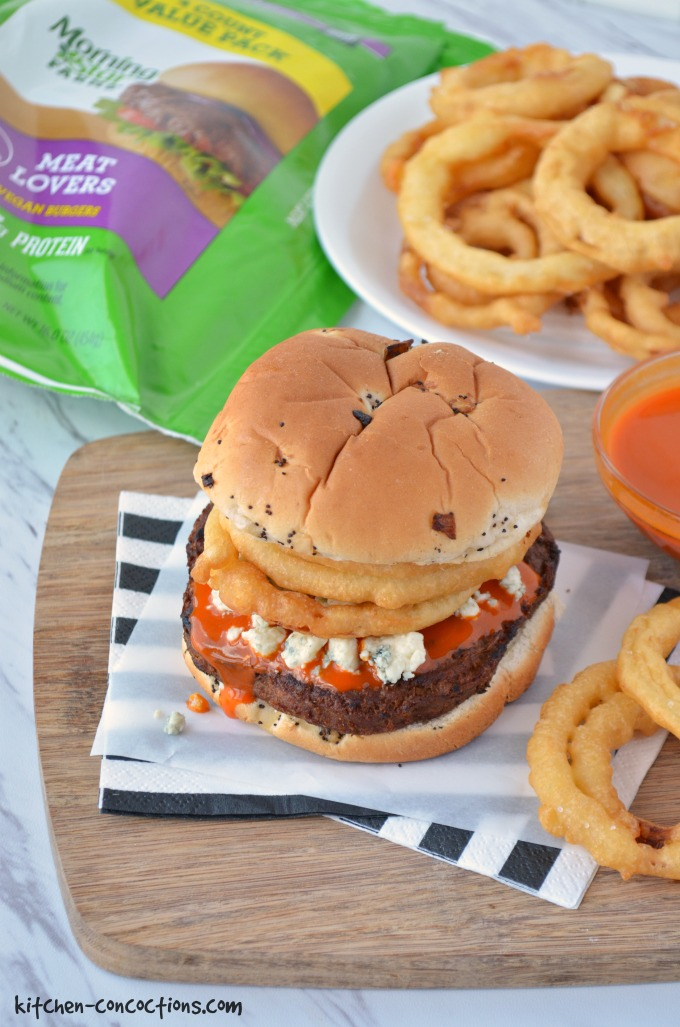 veggie burger on onion bun topped with buffalo hot sauce, blue cheese crumbles and crispy fried onion rings