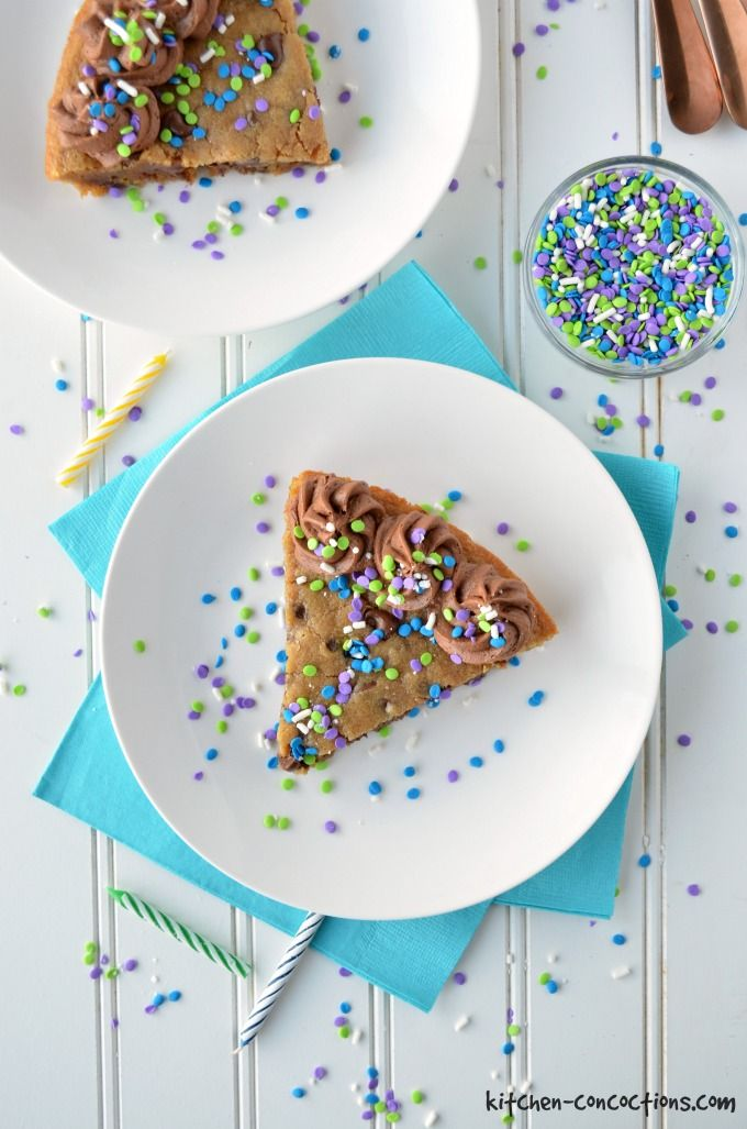 Chocolate Chip Cookie Cake with chocolate frosting, blue, purple and white sprinkles. Served on a white plate with blue napkins.