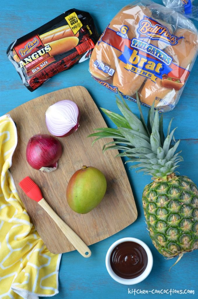 Hawaiian Hot Dogs image - mango and red onion on cutting board, whole pineapple, bowl of BBQ sauce, package of hot dogs and hot dog buns