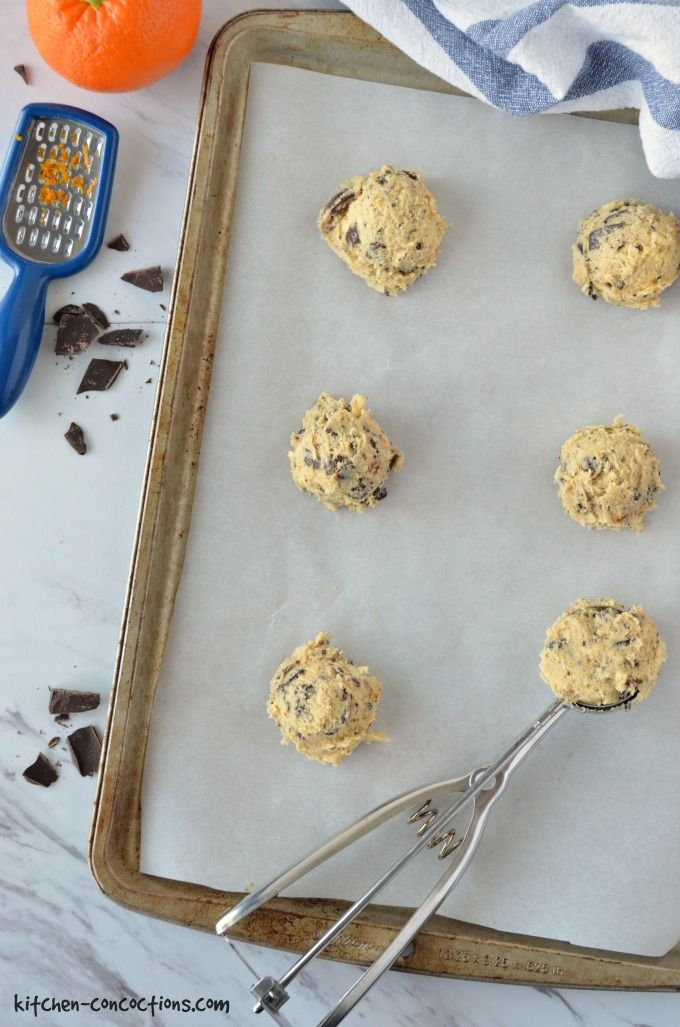 Orange Dark Chocolate Chunk Cookie dough scooped out on a baking sheet.