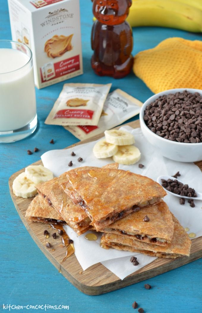 Peanut Butter and Banana Quesadillas cut into quarters, drizzled with honey and served on a cutting board placed on a teal backdrop. A glass of milk, honey bear, packets of Windstone peanut butter, and bowl of mini chocolate chips are in the background.