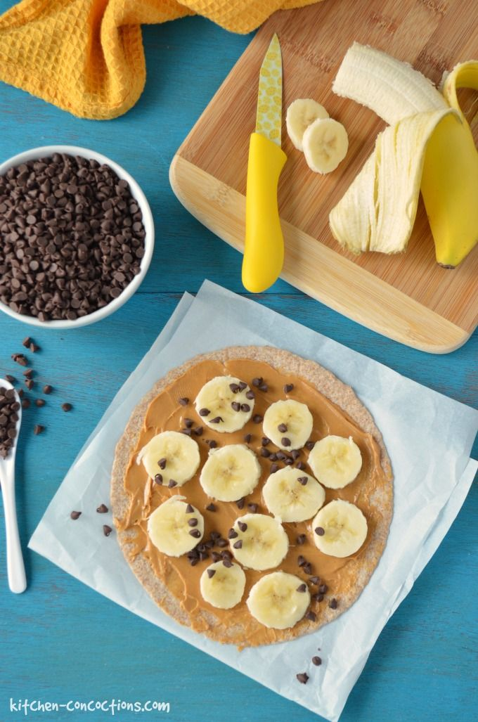 A whole wheat tortilla on top of parchment paper topped with peanut butter, sliced bananas and mini chocolate chips.