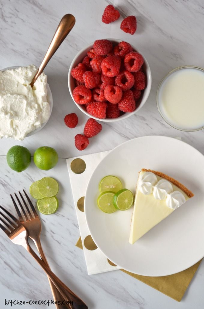 Ingredients for a Raspberry Key Lime Pie Milkshake including raspberries in a white bowl, homemade whipped cream in a white bowl with a gold spoon, a slice of key lime pie on a plate with a gold napkin and milk in a glass bowl.