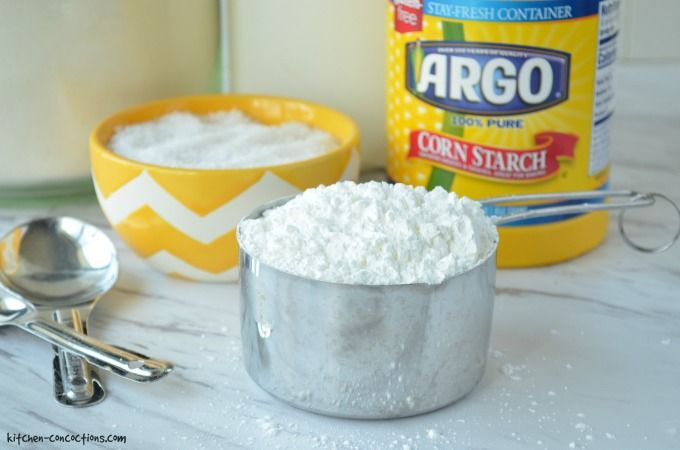 A metal measuring cup of corn starch with a container of Argo corn starch.