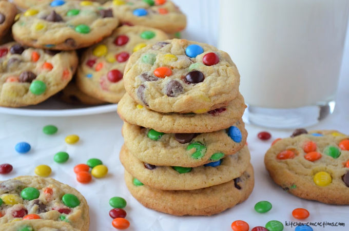 The Best M&M's Cookies stacked on top of each other next to a glass of milk and a white plate topped with cookies in the background