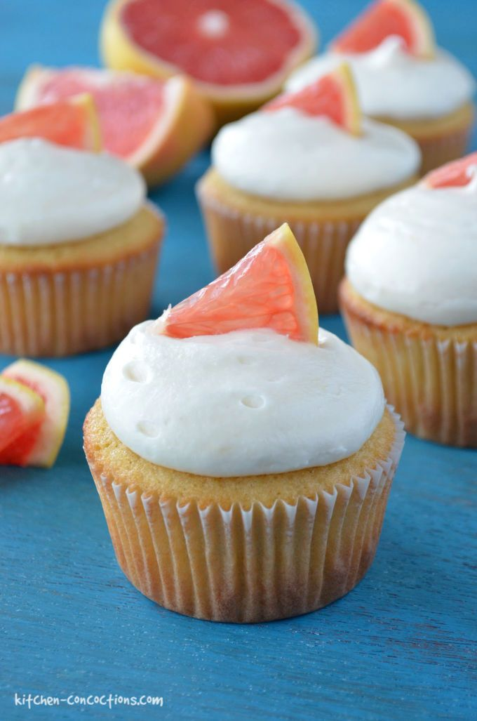 pink grapefruit cupcakes with cream cheese frosting a little slice of grapefruit on a piece of teal wood with a sliced grapefruit in the background