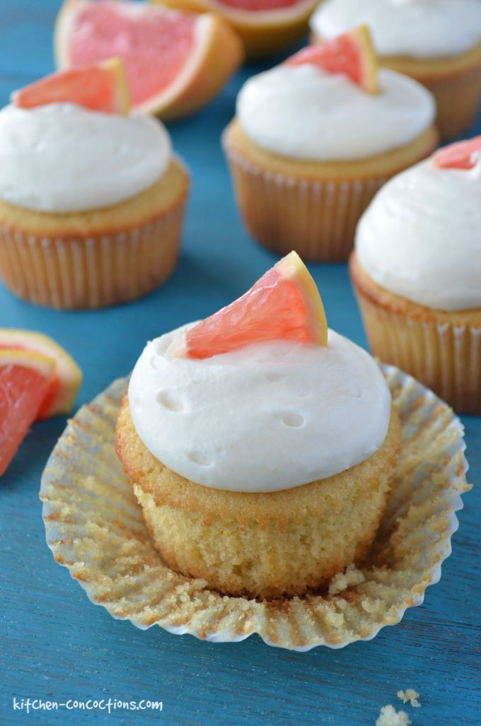 pink grapefruit cupcakes with cream cheese frosting a little slice of grapefruit, cupcake wrapper peeled back, sitting on a piece of teal wood