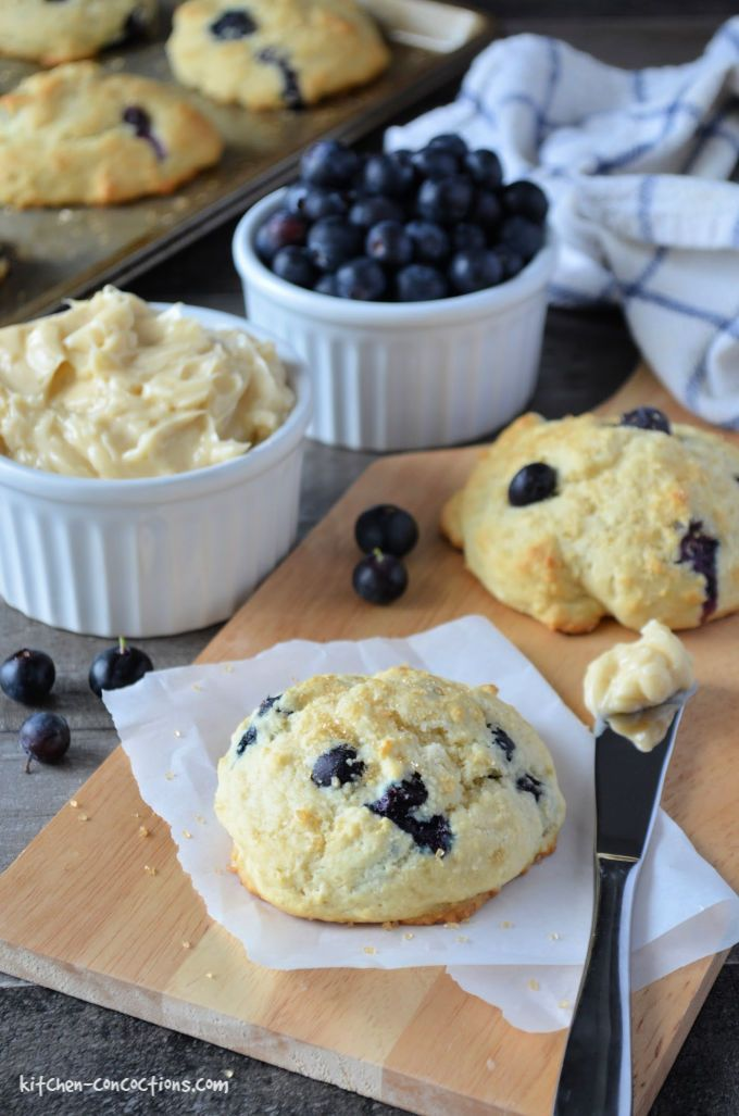 Blueberry Biscuits on a cutting board with a knife and a white bowl filled with vanilla honey butter and a bowl of fresh blueberries near by.