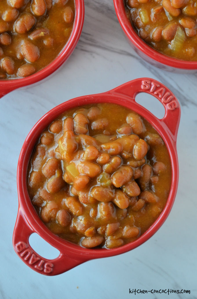 Close up overhead shot of Easy Baked Beans served in 3 mini red Dutch ovens.