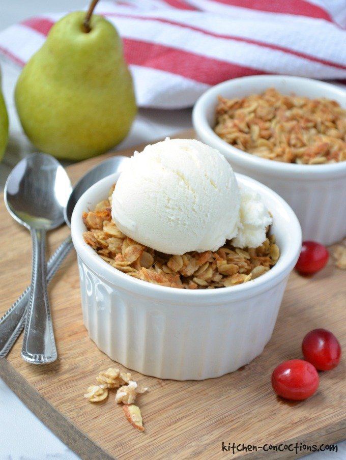 Cranberry Pear Crisp in a white ramekin topped with vanilla ice cream sitting on a wooden cutting board with a spoon next to it.