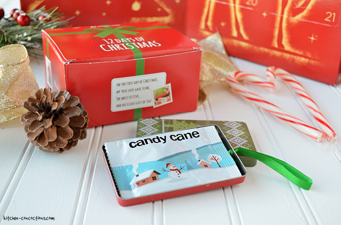 package of candy cane tea sitting next to a red tea box with gold ribbon, pinecones and candy canes for decoration