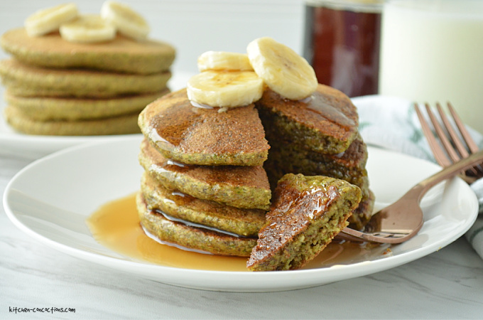 a stack of spinach pancakes topped with sliced bananas and maple syrup with a section sliced out and a jar of maple syrup and glass of milk in the background
