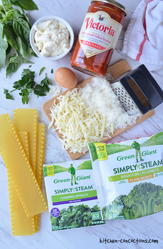 overhead shot of ingredients for Vegetarian Lasagna Roll Ups with dry lasagna noodles, packages of frozen spinach and broccoli, cheese grater and grated cheese on a small wooden cutting board, brown egg, jar of pasta sauce, bowl of ricotta, fresh basil and parsley