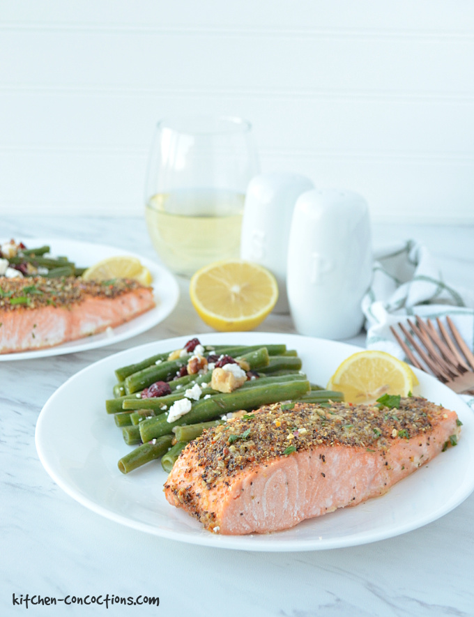 two white plates with a piece of lemon pepper salmon, a side of green beans, fresh lemon slices and a green and white striped towel, whole lemon, glass of white wine, two gold forks and a white salt and pepper shaker on the side