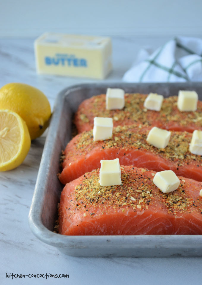 silver baking dish with three pieces of raw salmon topped with lemon pepper seasoning and cubes of butter with a stick of butter, green and white towel and whole lemon in the background