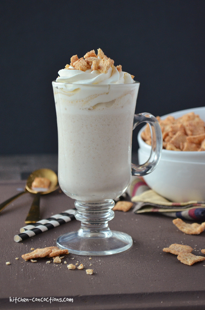 Coffee Cinnamon Toast Crunch Milkshake served in a milkshake glass with two black and white striped straws, on a brown board with a white bowl filled with cinnamon toast crunch cereal and a gold spoon