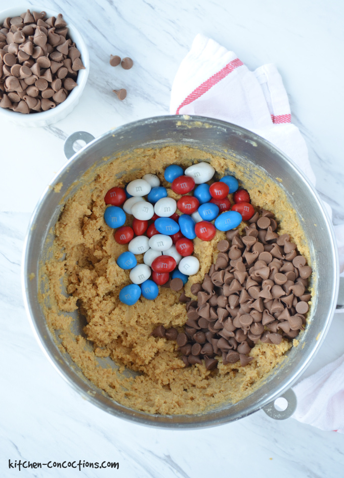 Overhead photo of a bowl of Peanut Butter S'mores Cookie dough with chocolate chips and M&M's sitting on top of the dough. A white bowl filled with chocolate chips is sitting next to the metal bowl with cookie dough and a white towel with a red stripe is also next to the bowl.