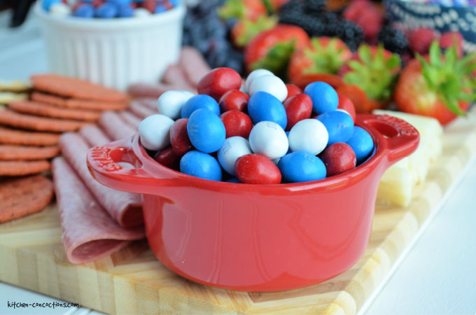 close up photo of a red bowl filled with red, white and blue M&M's