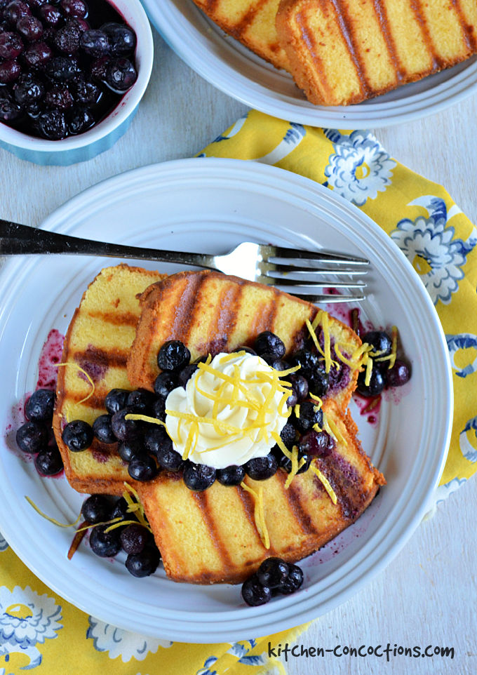 Grilled Pound Cake with Blueberries and Lemon Honey Whipped Cream served on a white plate set on a yellow napkin with blue flowers with a plate of grilled pound cake and bowl of blueberry compote in the background