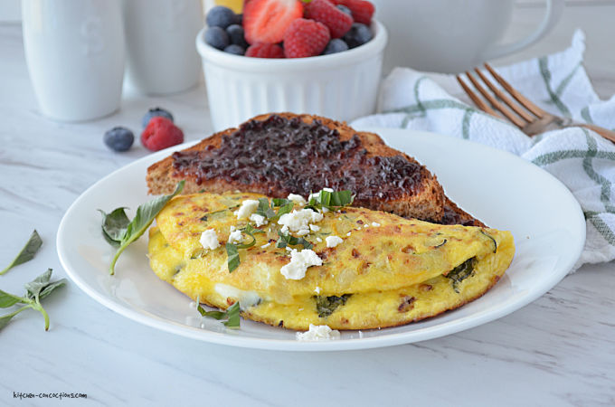 Summer Veggie Omelet served on a white plate with a piece of toast covered in blackberry jam, in the background is a white bowl with berries, white salt and pepper shaker, a white and green striped napkin with a gold fork.