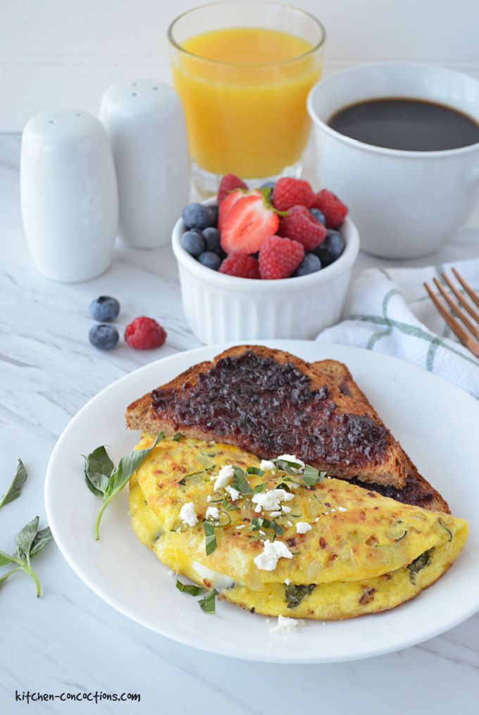 Summer Veggie Omelet served on a white plate with a piece of toast covered in blackberry jam, in the background is a white bowl with berries, glass of orange juice, white coffee cup filled with coffee, white salt and pepper shaker, a white and green striped napkin with a gold fork.