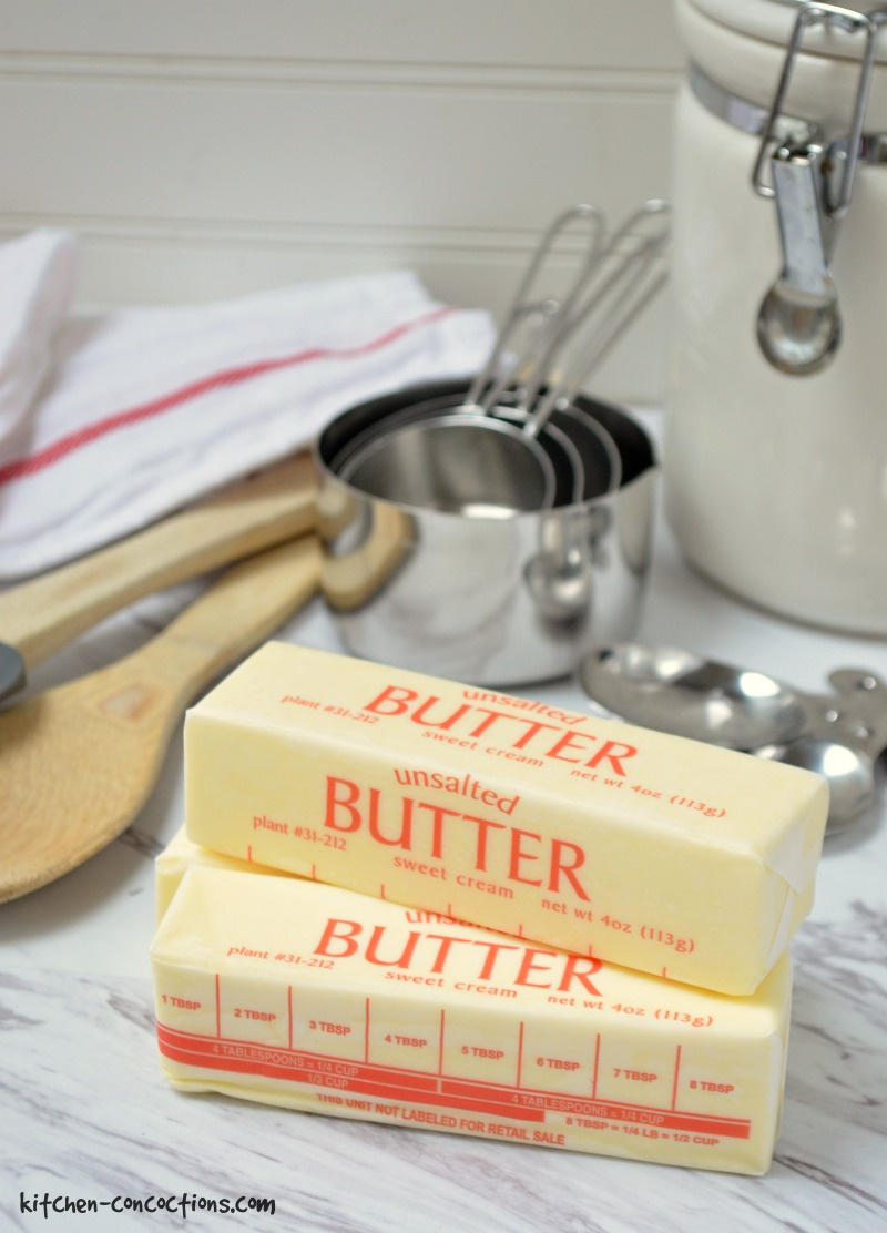 sticks of butter on a counter with measuring cups and spoons in the background