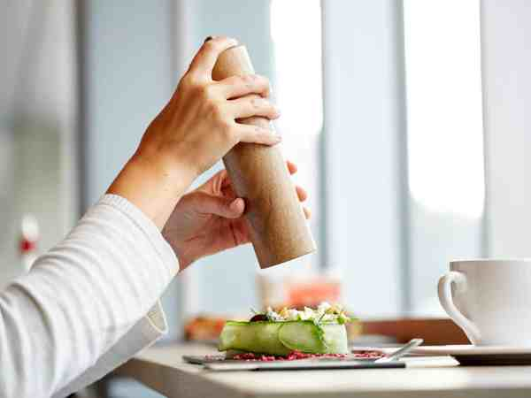 food, culinary, eating and people concept – woman hand with salt shaker seasoning brie cheese salad at restaurant or cafe
