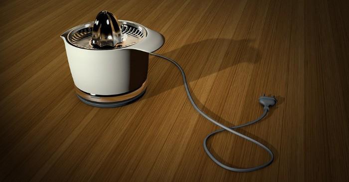 Eine elektrische Orangenpresse mit Auffangbehälter und Kabel auf Holzoberfläche.