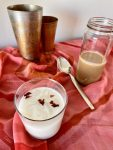 A glass of thandai with bottle of homemade concentrate in the background