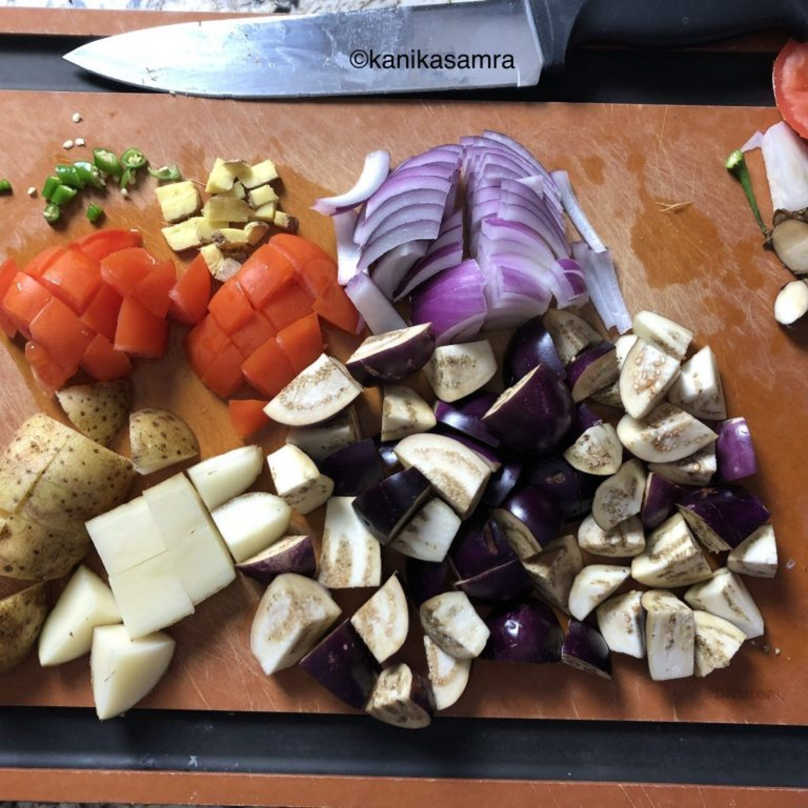 Ingredients for Aloo Baingan chopped on a chopping board
