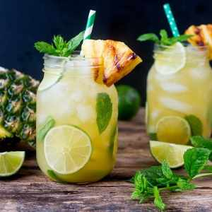 Pineapple Ginger Mojitos with Spiced Rum - a sweet and spicy twist on the classic mojito cocktail. Served with a wedge of caramelized pineapple.