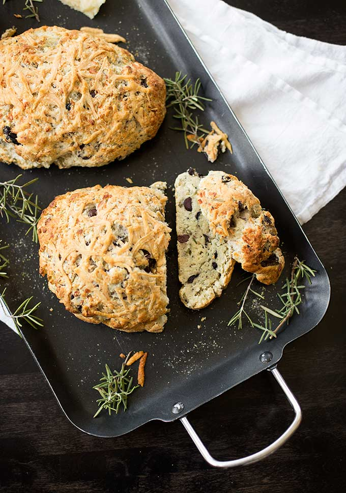 This Rosemary-Olive Soda Bread recipe combines fresh rosemary and kalamata olives into a simple but delicious soda bread. Topped with parmesan cheese.