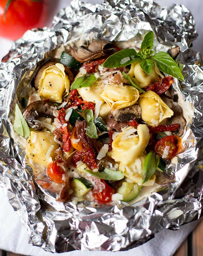 Italian Tin Foil Dinners - a fun spin on the classic foil dinner. Cheese tortellini, fresh veggies, and lots of cheese make for a tasty and easy meal!