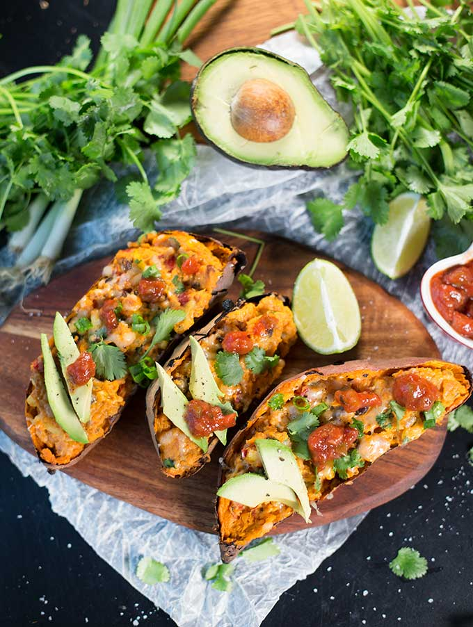 Mexican Stuffed Sweet Potatoes - simple to make, but full of flavor! Bursting with corn, peppers and beans, these make the perfect healthy weeknight dinner!