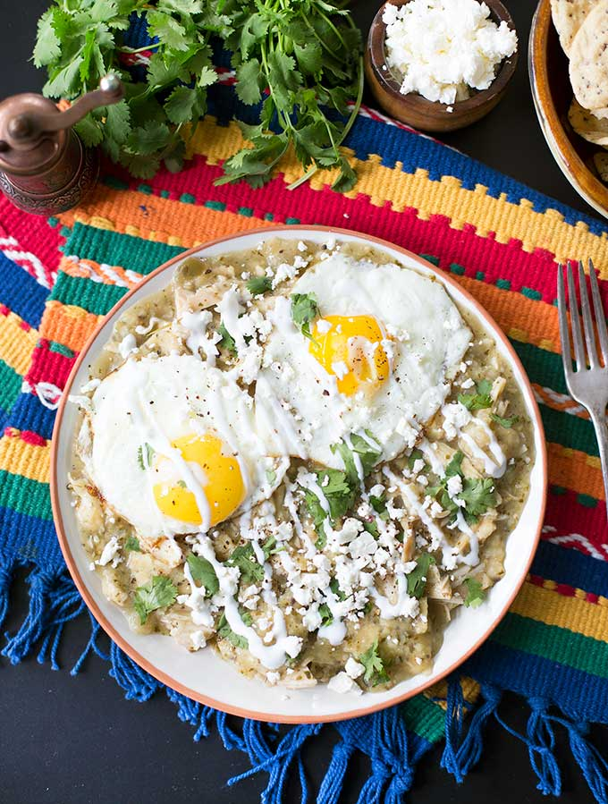 Chicken Chilaquiles - an authentic Mexican dish combining chicken, salsa verde, and corn tortillas. Topped with fried eggs, fresh cilantro and feta cheese!