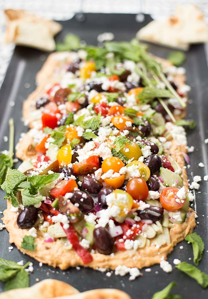 Greek Seven-Layer Dip: Loads of Mediterranean flavors: hummus, olives, peppers, feta, cucumbers, tomatoes, mint. The perfect layered dip for pitas.