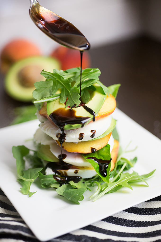 Peachy Caprese Stack - layers of fresh peaches, avocado, mozzarella cheese and basil, stacked together and drizzled with a balsamic reduction.