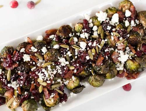Roasted Bacon Cranberry Brussels - the right way to eat brussel sprouts! Roasted in EVOO and tossed with goat cheese, cranberries, bacon and pepita seeds.