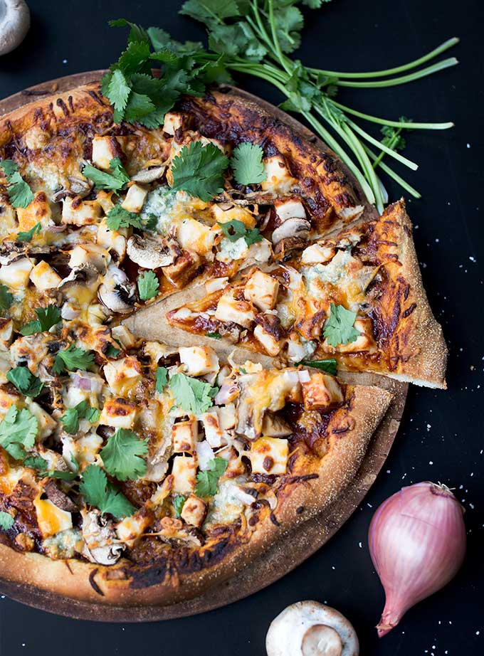 Classic BBQ Chicken Pizza: An easy-to-make crust topped with all the traditional toppings: bbq sauce, roasted chicken, mushrooms, cheeses and fresh cilantro. It's a classic!