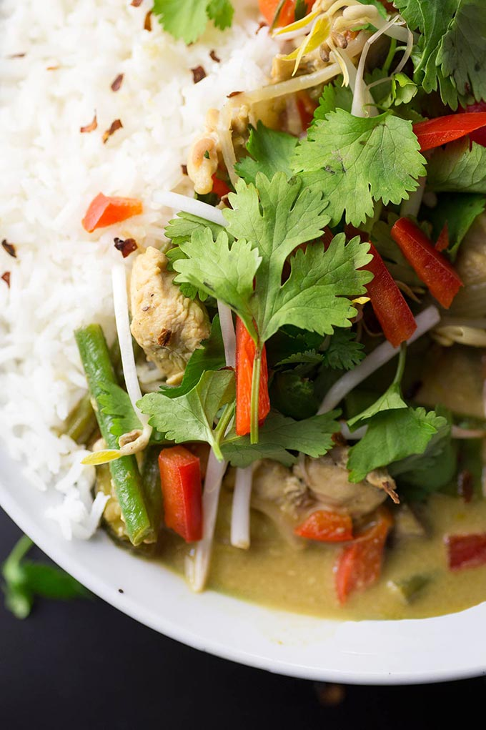 Simple Green Curry - tender chicken and sautéed veggies swimming in a creamy coconut curry sauce. Served over rice and garnished with fresh cilantro and crushed nuts.