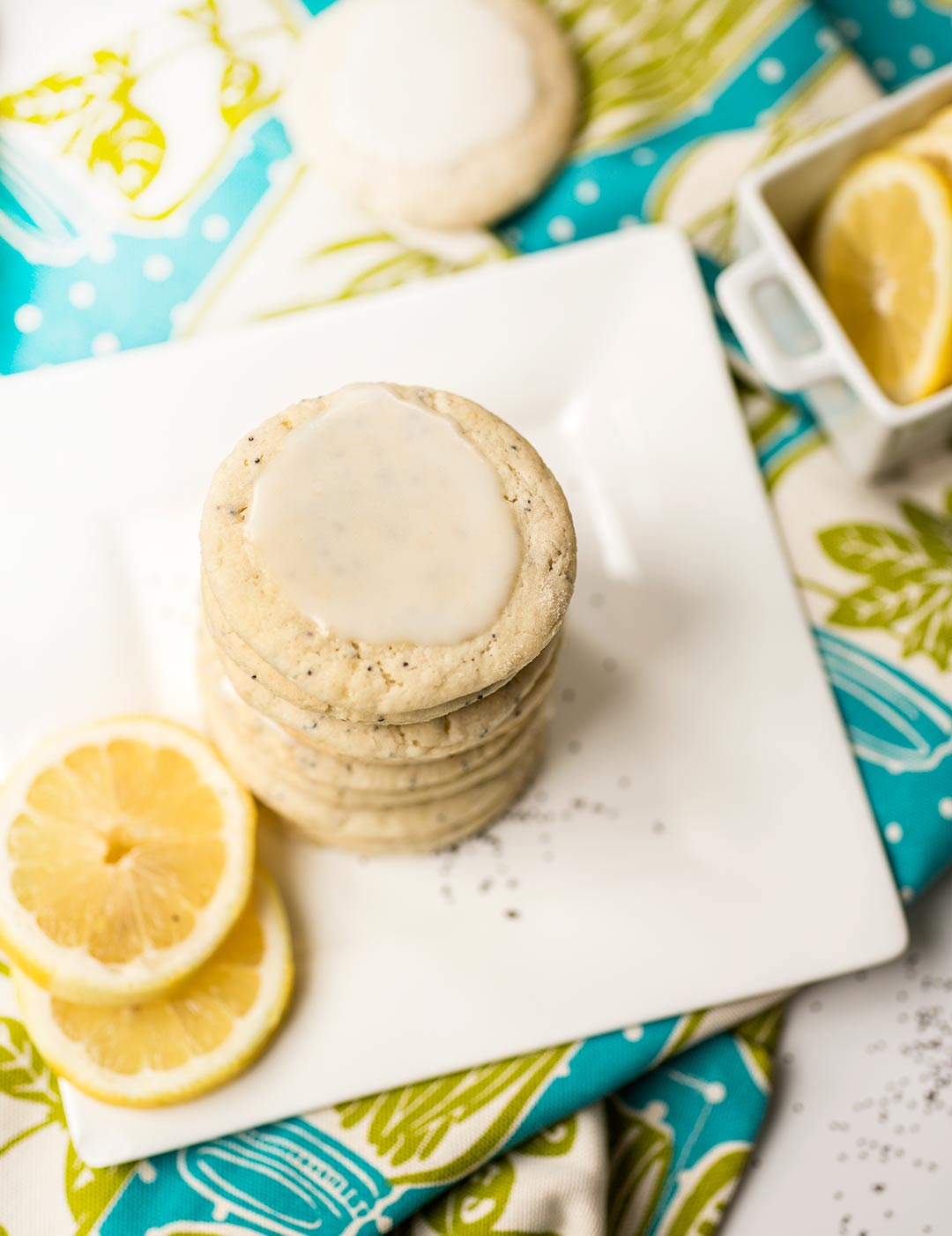 Lemon Poppy Seed Cookies - a soft, lemony cookie full of poppy seeds and drizzled with a sweet powder-sugar glaze. The perfect party treat!