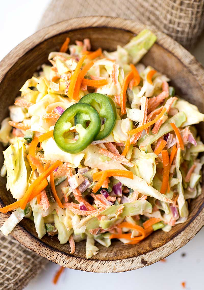 Quick and Easy Spicy Coleslaw – shredded cabbage and carrots, diced jalapeno and red onion are tossed with a spicy Cajun mayo sauce for a creamy slaw that's full of flavor!