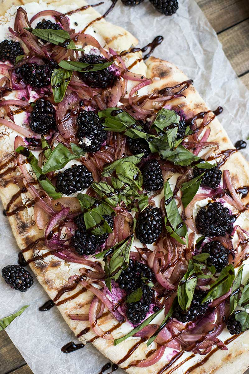 Goat Cheese and Blackberry Flatbread Pizzas: A homemade flatbread crust, grilled, and topped with fresh berries, melty cheese, fresh basil and sweet onions.